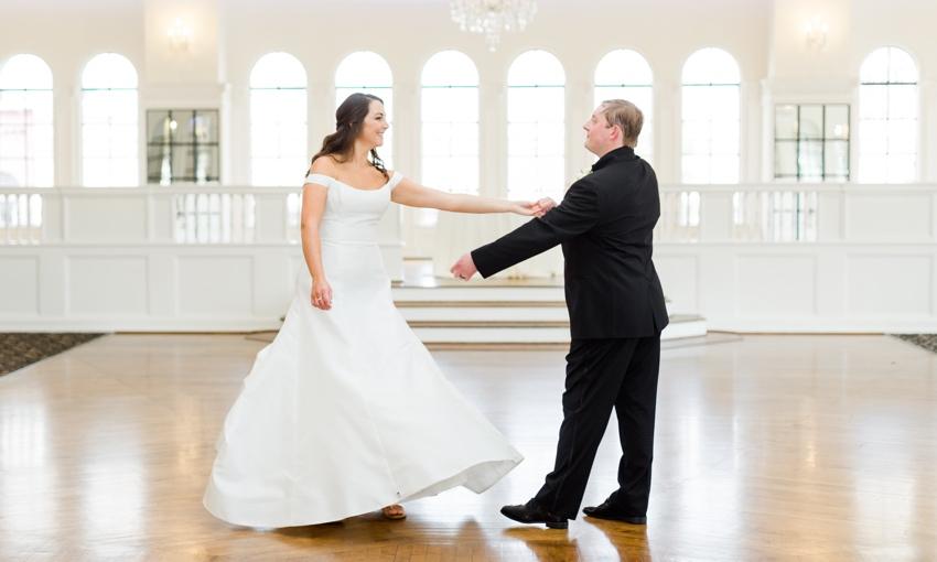 groom twirling bride in ballroom