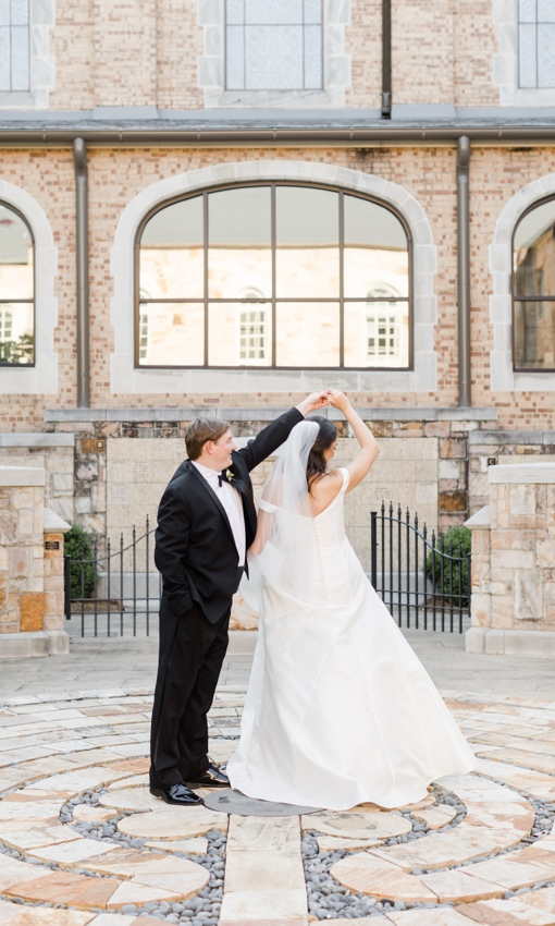 groom twirling bride outside of church